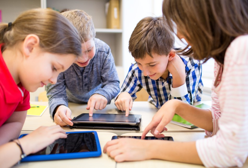 roup of school kids in elementary school learning with tablets